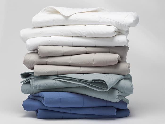 various organic comforters stacked on top of each other