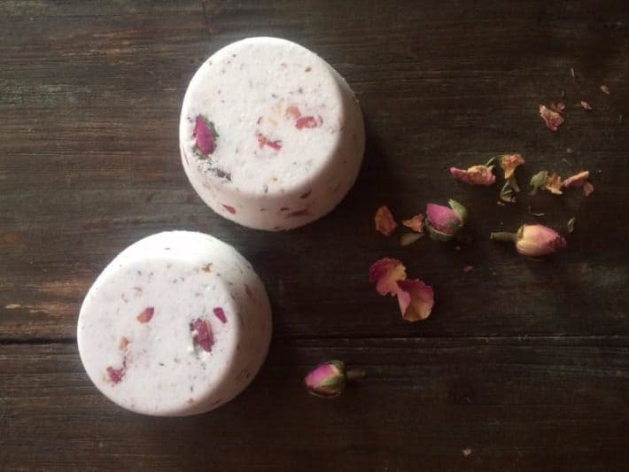 two bath bombs laid out on table with rose petals