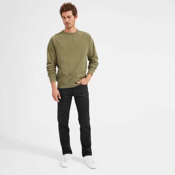 man wearing green sweater and black jeans and white sneakers