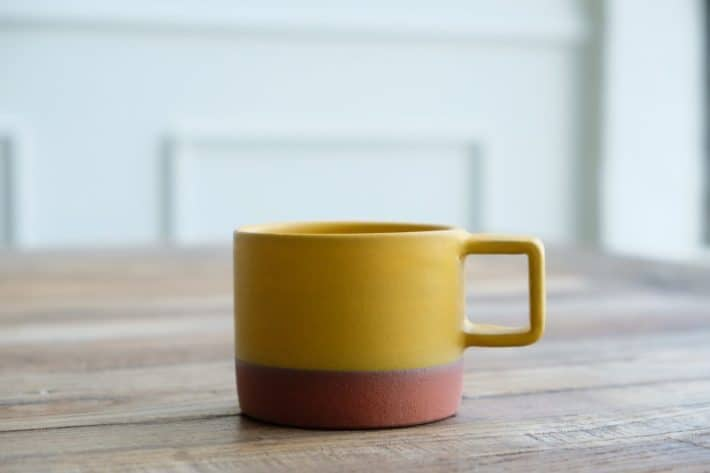 yellow and brown mug placed on a wooden table