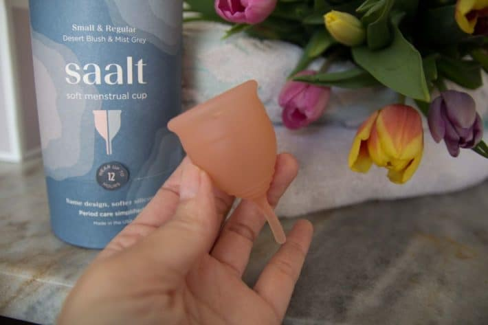 hand holding up a Saalt menstrual cup with the product box in background