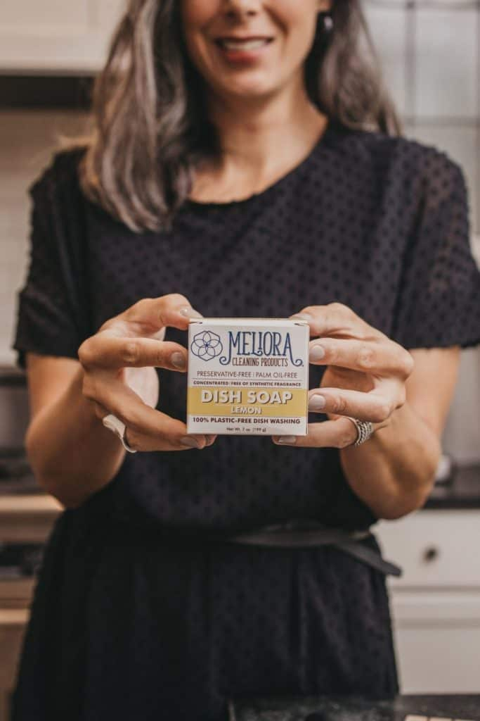 Lisa holding the packaging for Meliora dish soap