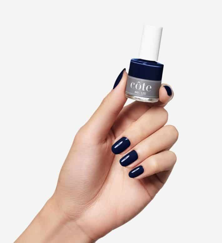 hand holding bottle of Cote dark midnight blue nail polish