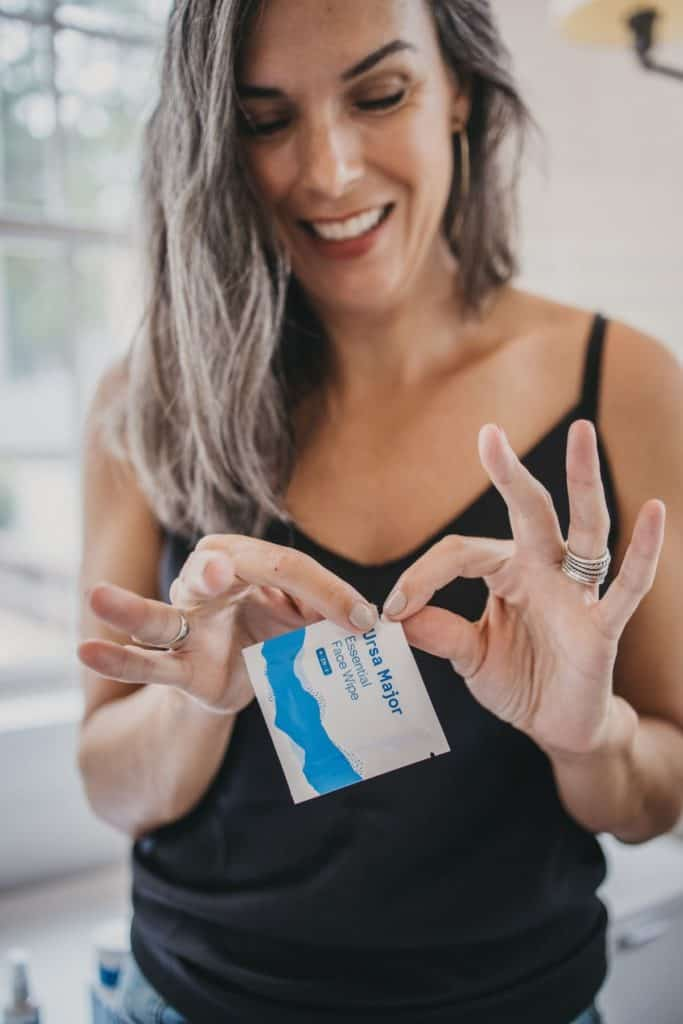 Lisa opening a packet of Ursa Major's face wipes