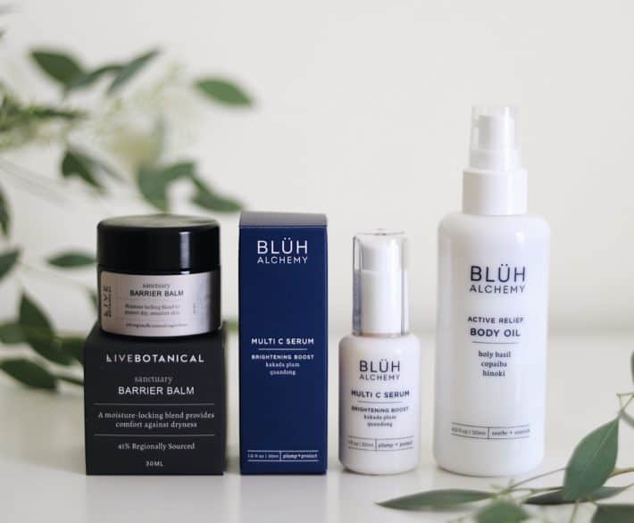 various LIVE BOTANICAL and BLUH ALCHEMY products styled together next to leaves