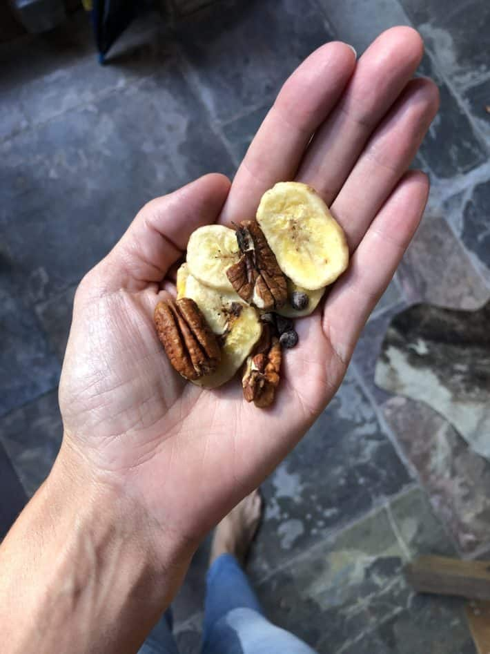 handful of banana chips and nuts in palm of a hand