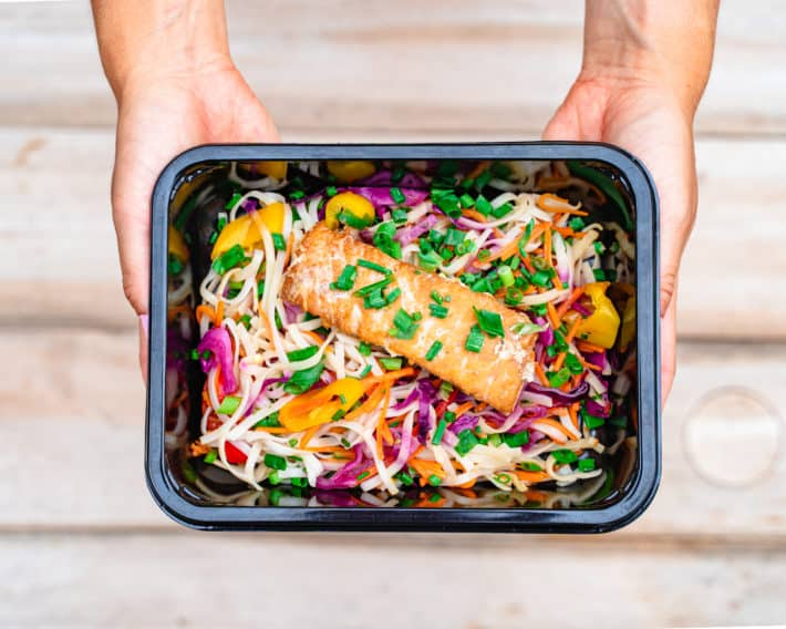 container of Nutrition for Longevity dinner option with fresh salmon