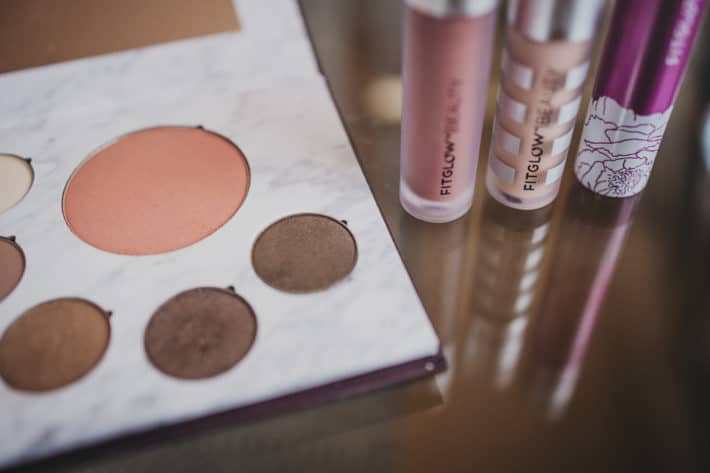 four makeup items on a glass table from fitglow