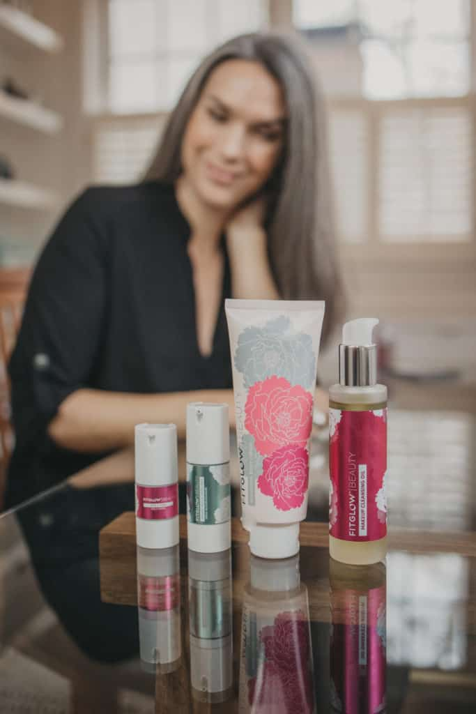 4 fitglow beauty products on a glass table