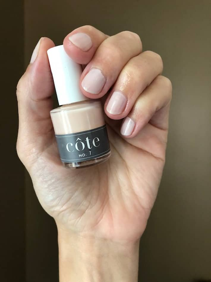 Hand holding Cote Nail polish in No. 7, a neutral almond shade.