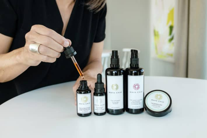 Maya Chia skincare lined up on a table with Lisa holding a dropper