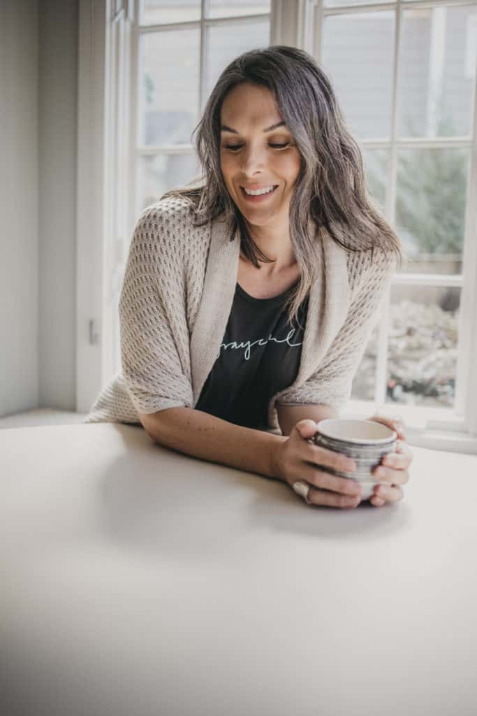 Lisa holding a coffee up at her counter