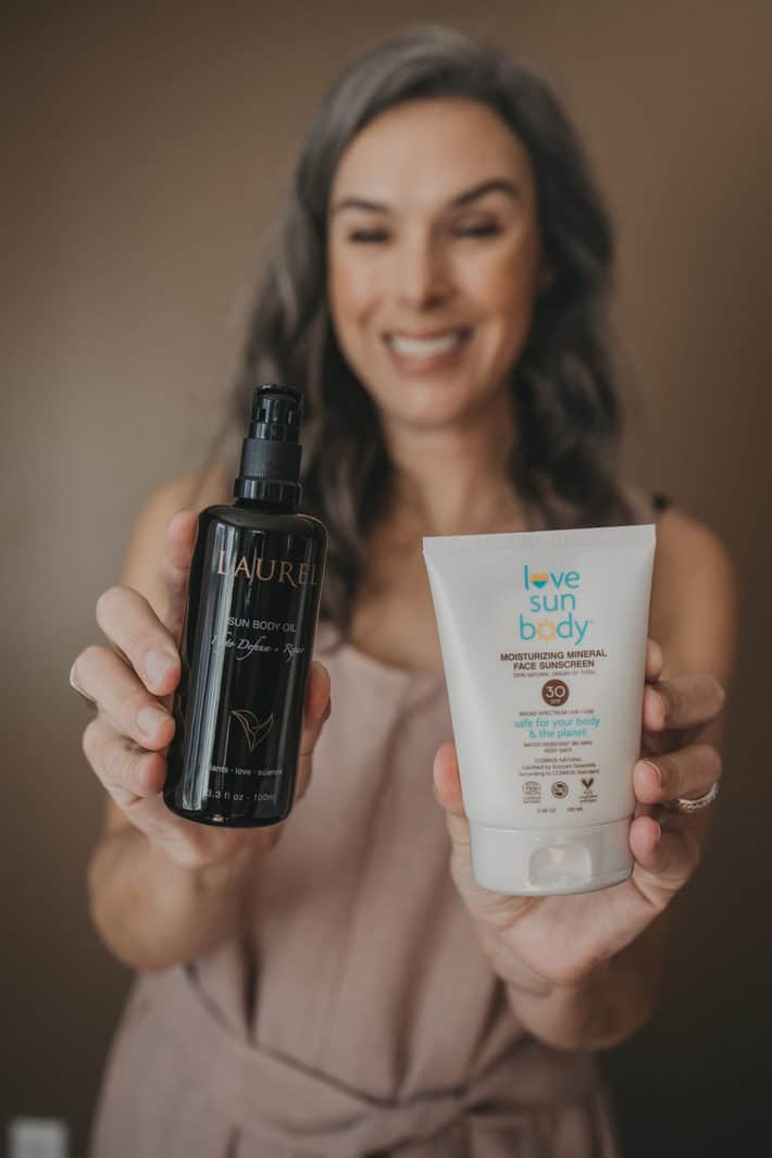 woman holding face oil and SPF cream