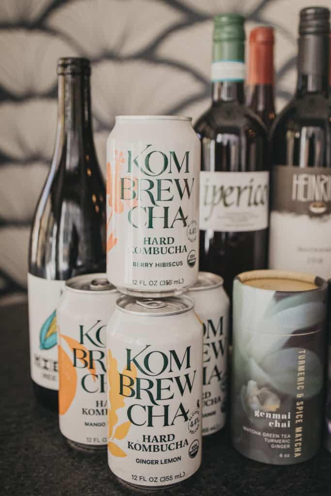 Cans of Kombrewcha stacked in front of wine bottles