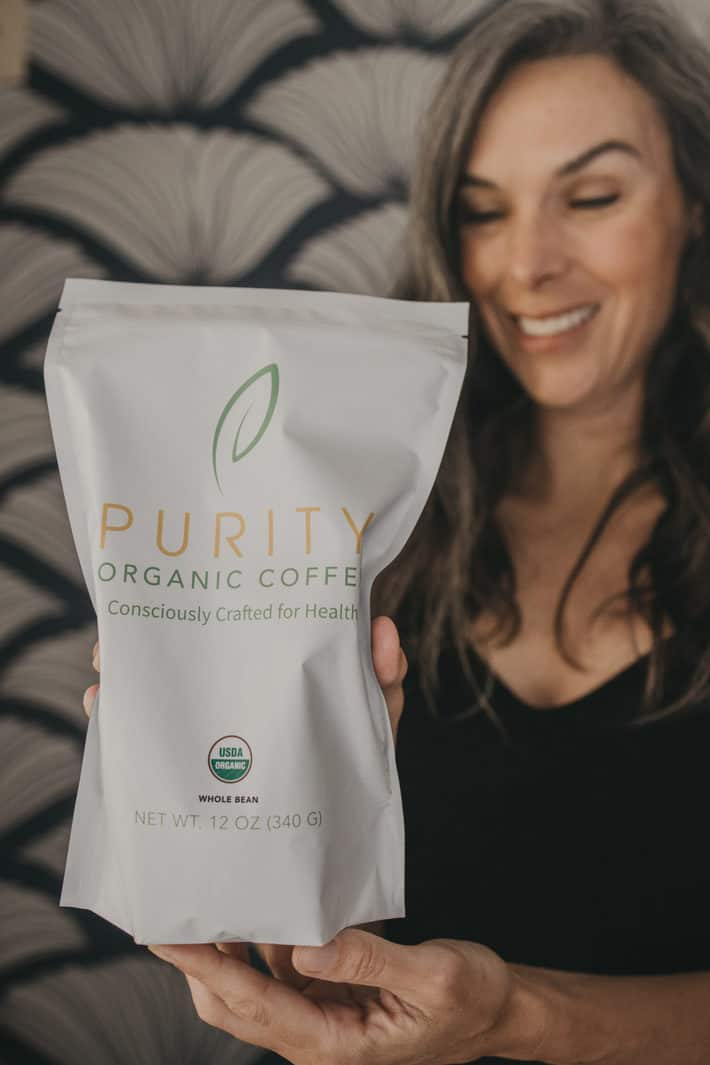 woman holding bag of purity coffee