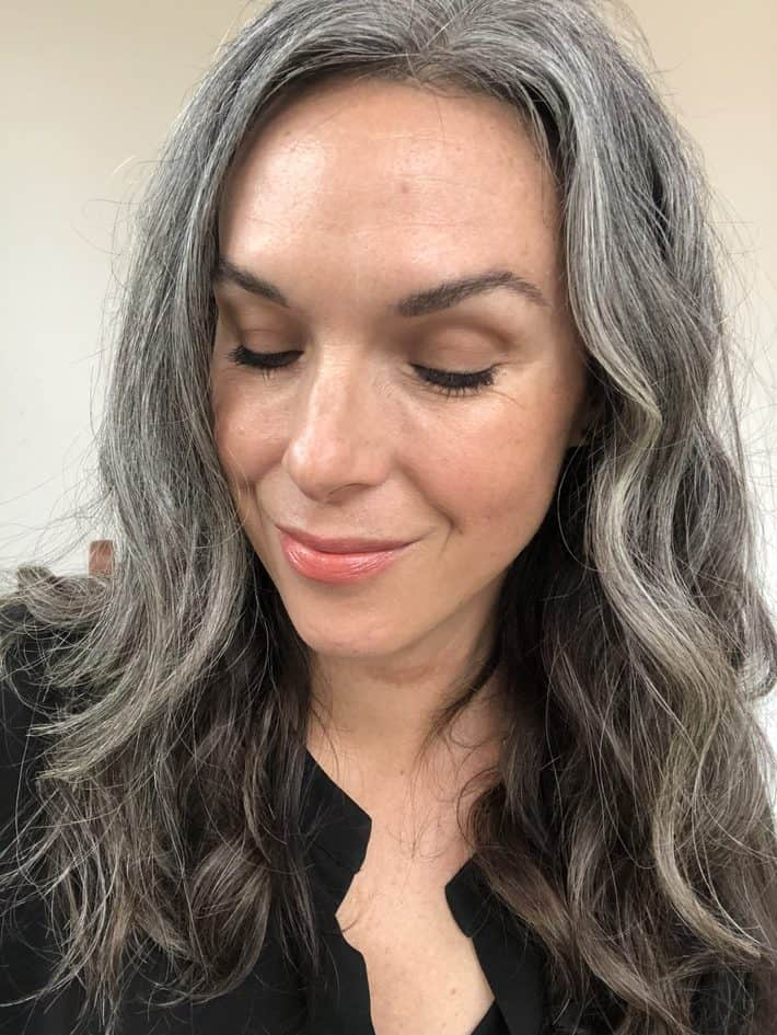 Lisa with wavy gray hair past her shoulders, smiles and looks down.