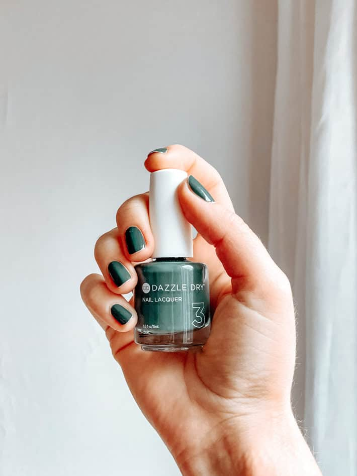 woman's hand holding a bottle of Dazzle Dry nontoxic nail polish in green