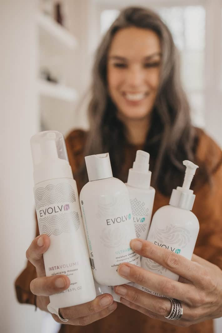 lisa holding EVOLVh shampoo and conditioner and volumizing mousse