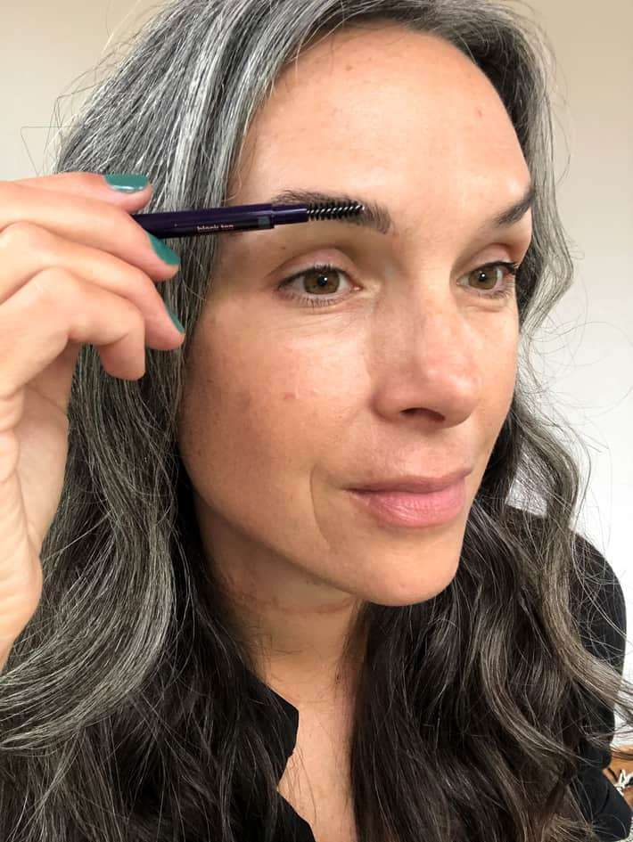 lisa buffing out brow filler with spoolie for a natural look