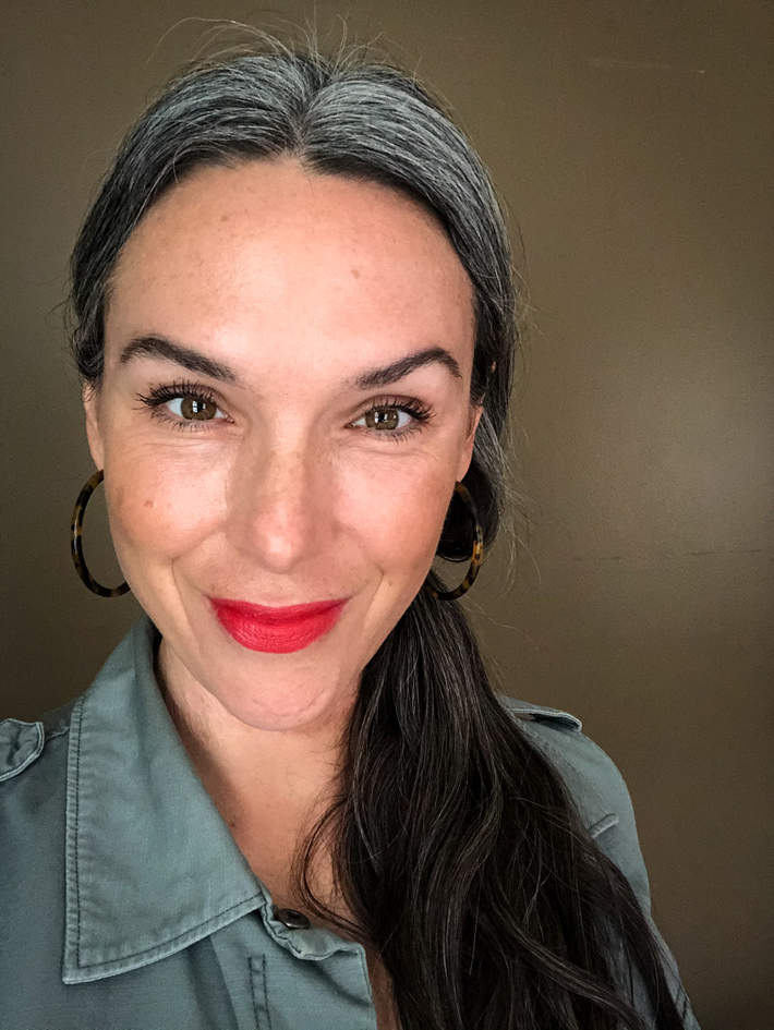 Lisa wearing ILIA Beauty lipstick in hot-red Flame, and Westman Atelier bronze highlighter in Brulee.