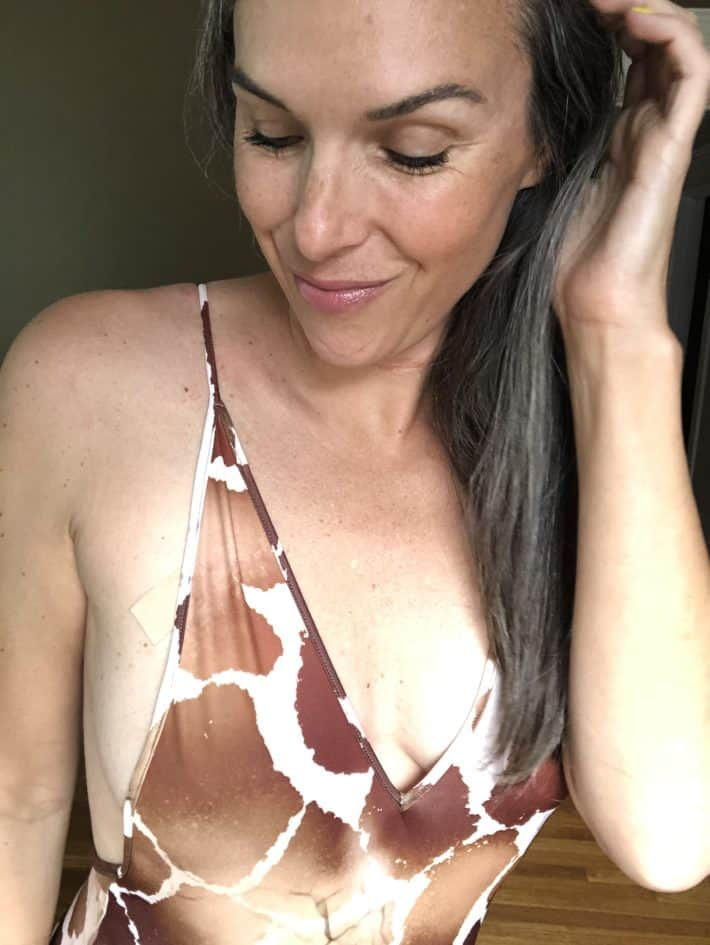 Lisa wearing a giraffe print one-piece swimsuit in a close up of her face.