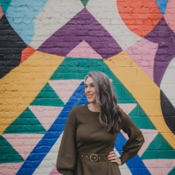 Lisa is standing in front of a multi-colored abstract painting on an outdoor wall, hand on hip.