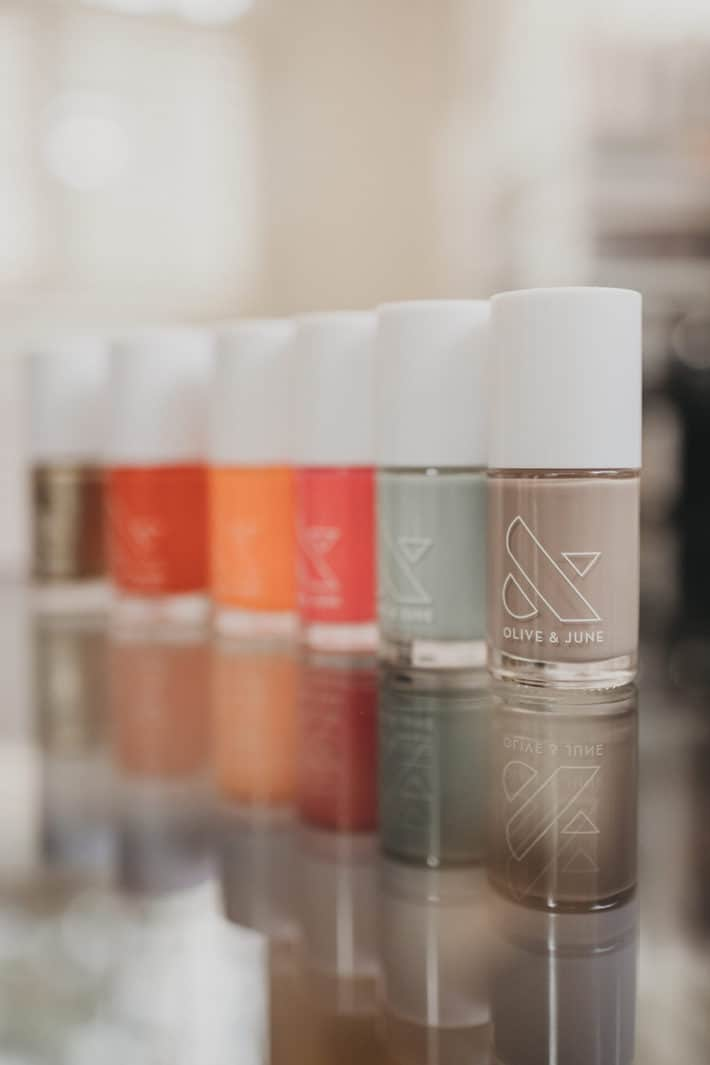 A row of bright summer nail polish bottles sit on a glass table.