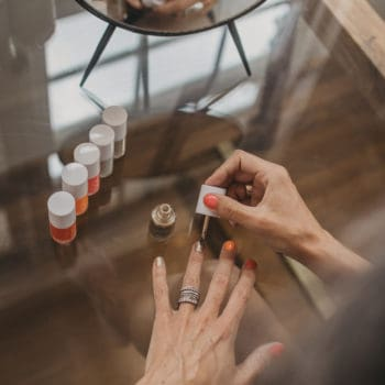 A woman paints her ring fingernail with metallic gold nail polish.