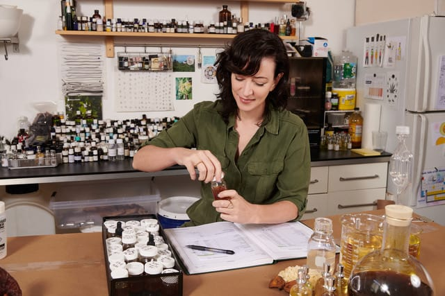 A brunette woman mixes ingredients in a lab.