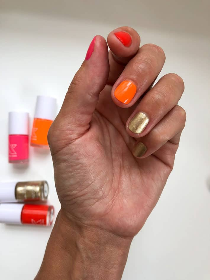 Lisa holds her hand in a light fist to showcase metallic gold nails.