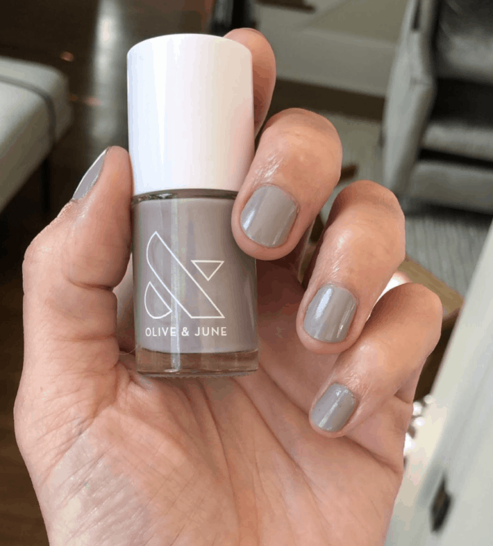 A hand holds up RP, a greige nail polish from Olive and June.