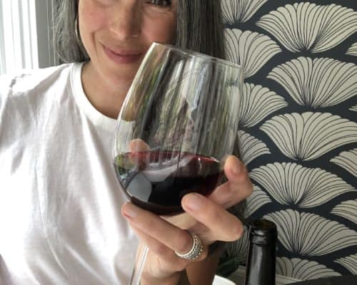 Lisa smiling and holding a glass of red wine.