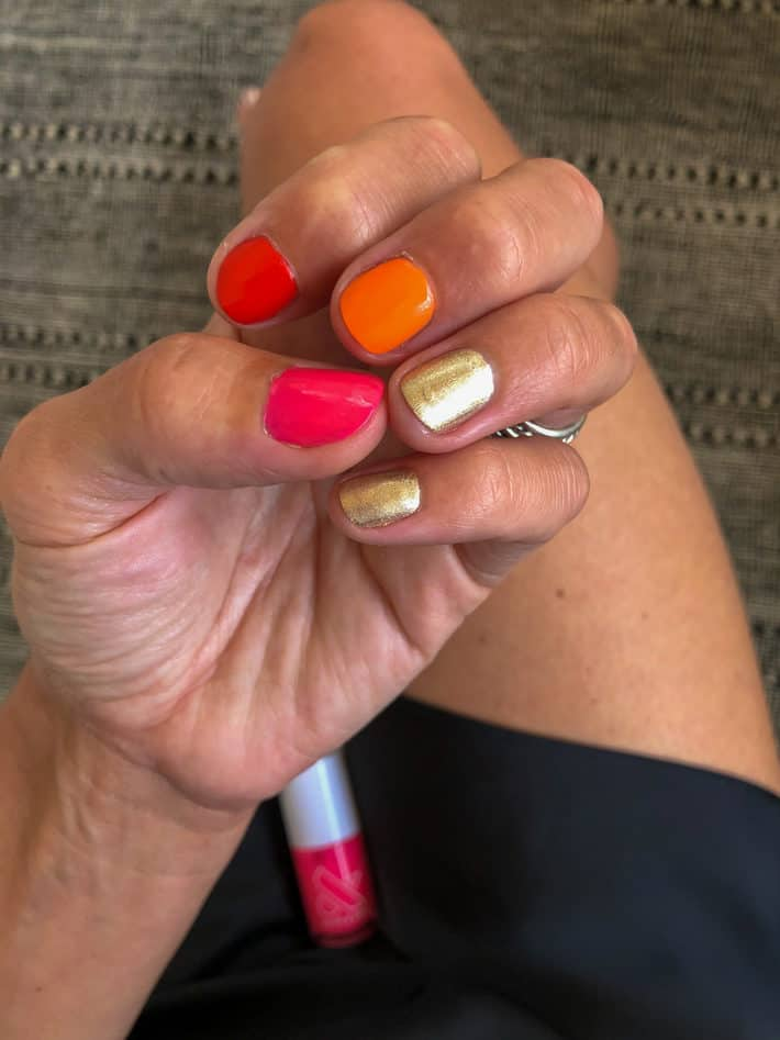 Lisa hold her hand in a light fist to show her multicolored nails.