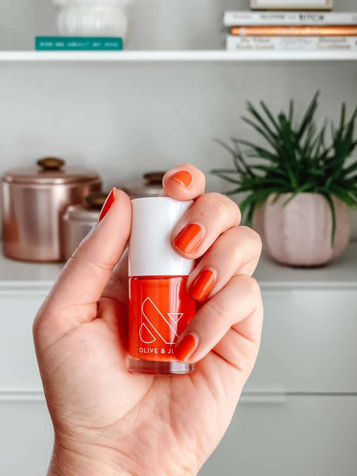 A hand holds up Lava, firey orange-red nail polish from Olive and June.