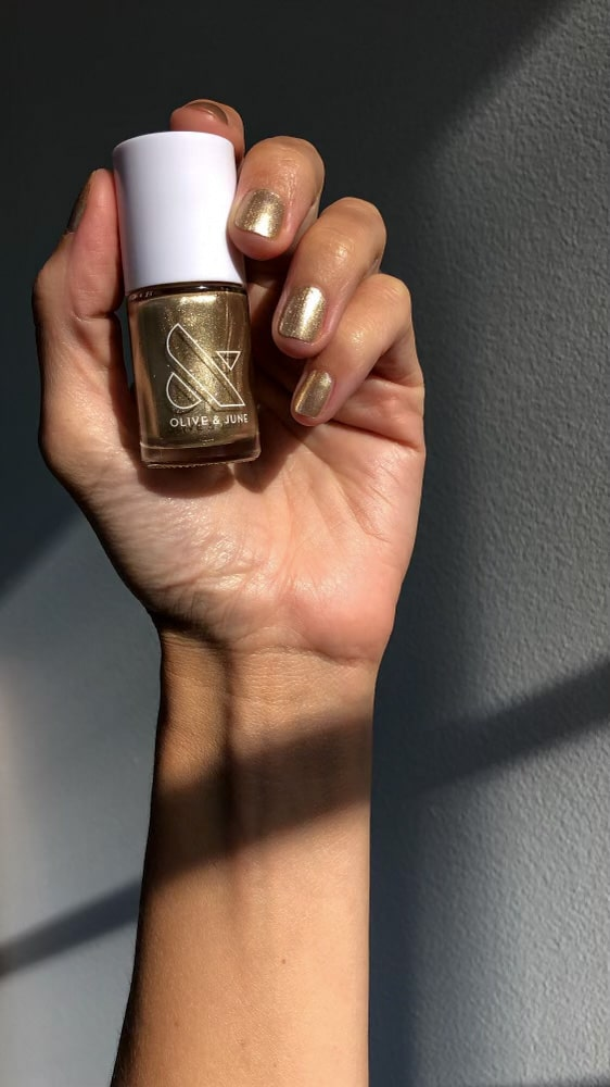 A woman shows off her gold manicure while holding the nail polish bottle.