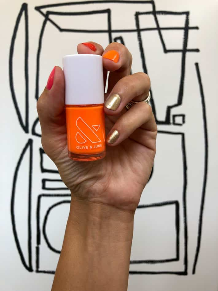 A hand holds up Orange Wedge, a bright orange nail polish from Olive and June.