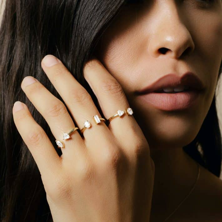 woman with dark hair wearing rings on all fingers