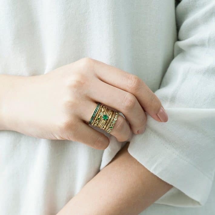 woman wearing sustainable ring with green stones