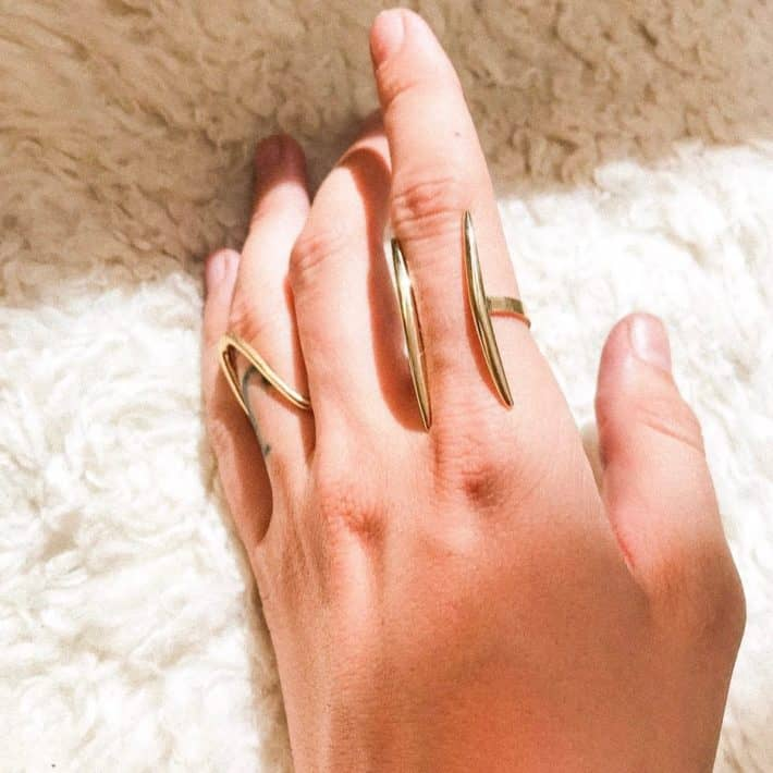 woman wearing two long rings from sustainable brand
