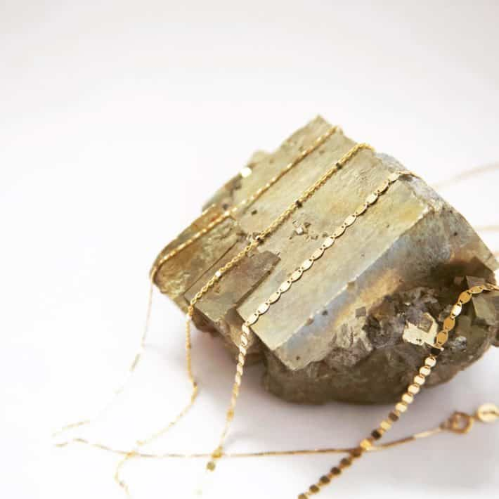 three gold necklaces made with sustainable materials