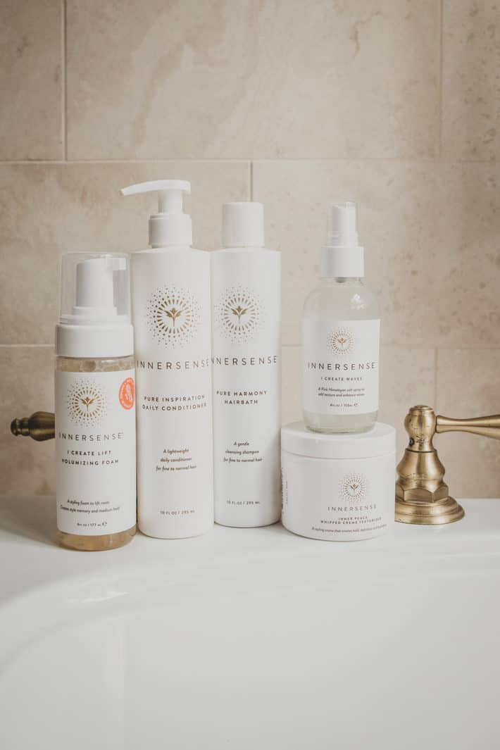 A stacked collection of Innersense hair products sits on a white bathroom sink.
