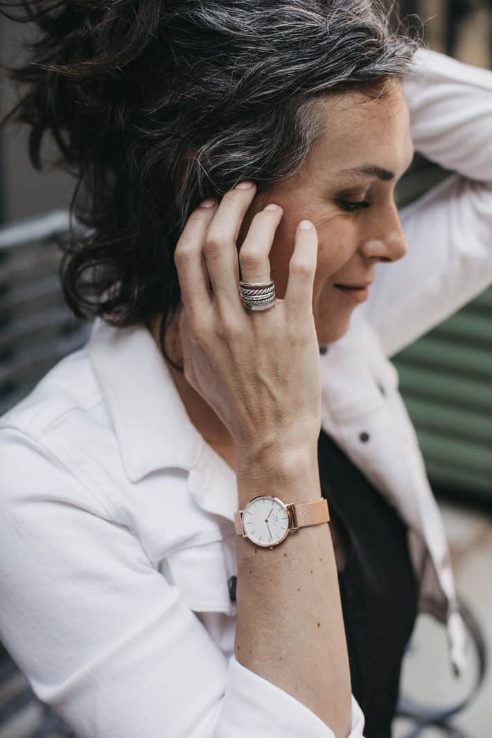 woman wearing ring and watch from sustainable jewelry brands