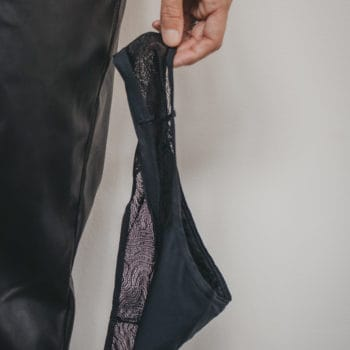 a woman holds a black lace thong in her left hand, down by her side.