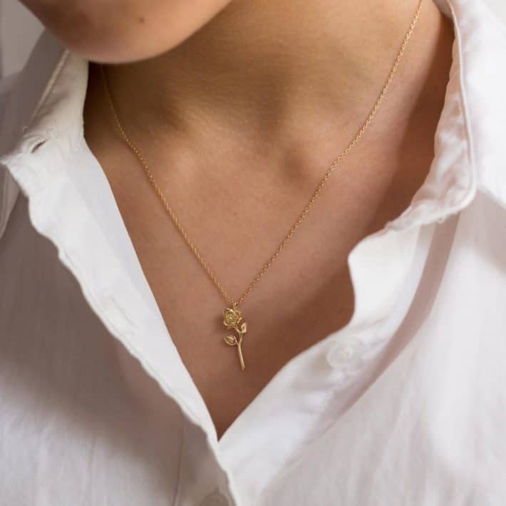 woman wearing sustainable rose shaped necklace