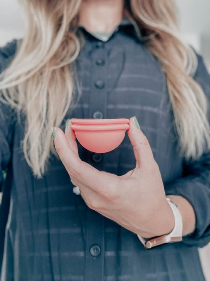 woman holding a pink reusable period cup