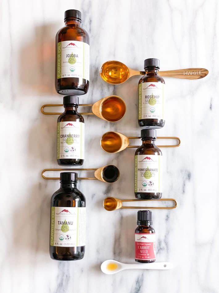 Bottles of facial oils lay on a marble stone next to gold measuring spoons.