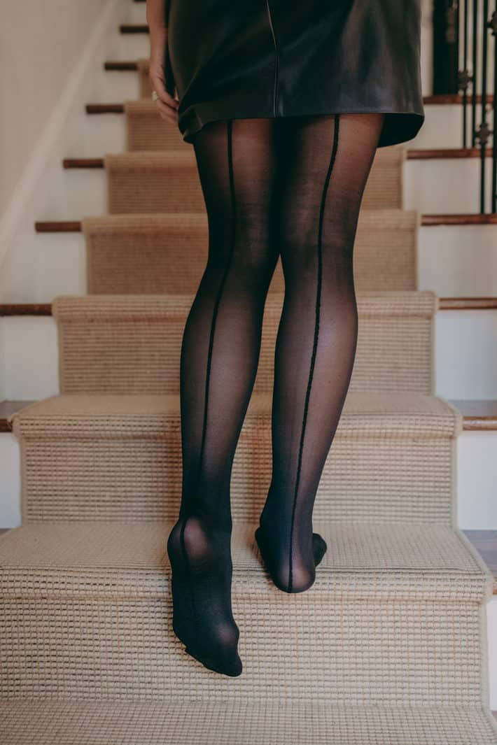 A woman walks up the stairs wearing backseam classic tights.