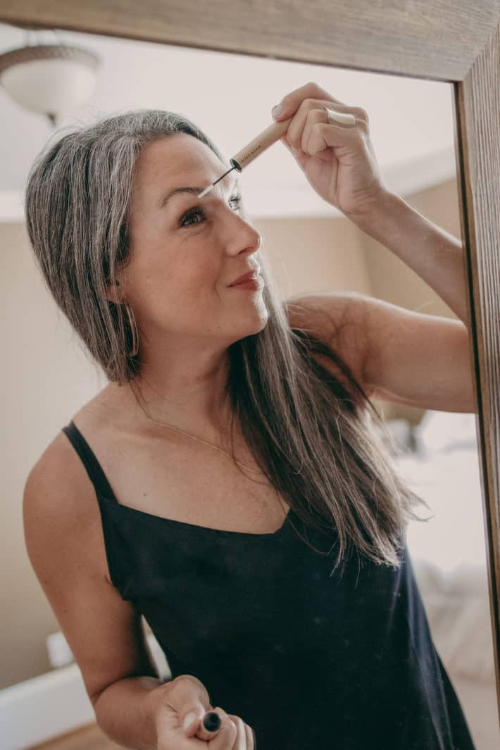 A woman stands in front of the mirror applying brow serum.