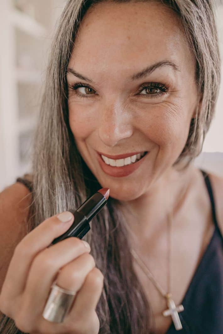 woman smiling and applying lipstick