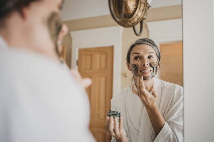 Lisa applies a green, honey-based face mask while looking in the mirror.